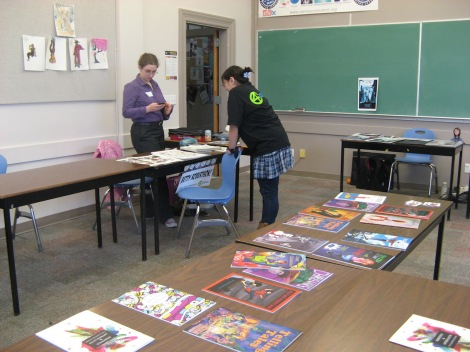 Two of my friends chat in the background while our comics from last year repose in glory on the central table.