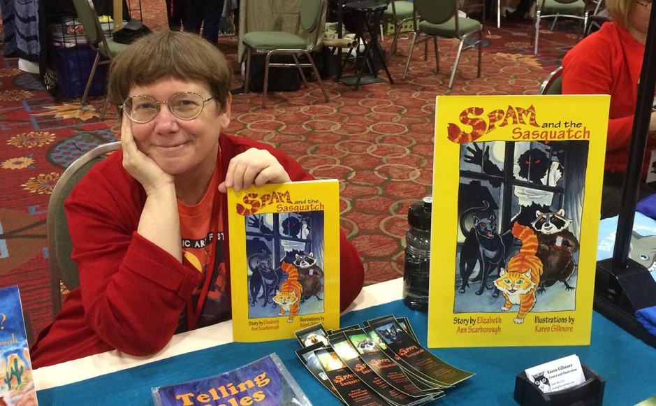 Me, proudly (or maybe smugly) showing off my proof copy of Spam and the Sasquatch at the artists' alley table at A-Kon in Dallas.