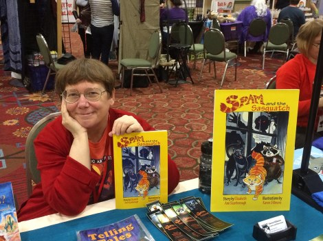 Me, proudly (or maybe smugly) showing off my proof copy of Spam and the Sasquatch at our artists' alley table.