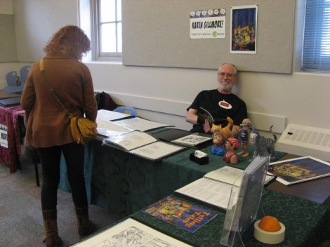 My table last year at CCAF (which was then called the Camosun College Comics Conference — we were into alliteration!). I got a luxurious amount of space last year! That's my handsome hubby, Ron, holding down the fort while I take pictures.