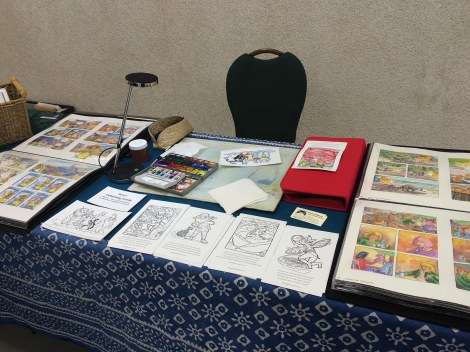 As is usual in Artist's Alley, artists were asked to demonstrate their work. I had a lot more elbow room to work here, and was able to set up my portfolios of originals on each side. I had also made some colouring cards of some of the Inktober drawings, and ended up painting two of them for the organizer for a demo.
